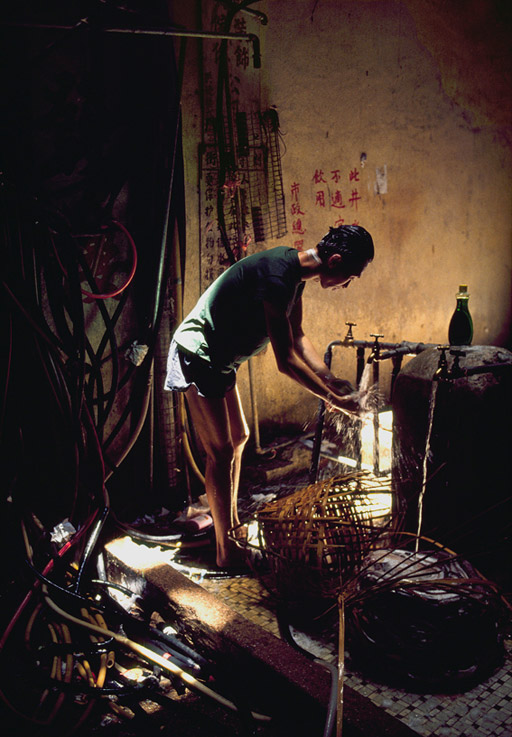 A man washes his hair at the stand-pipe