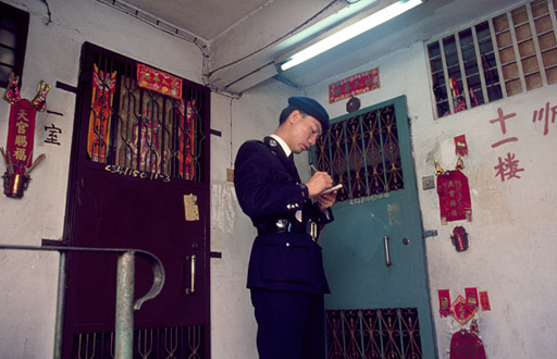 A policeman makes notes  on the 11th floor landing of an apartment block.