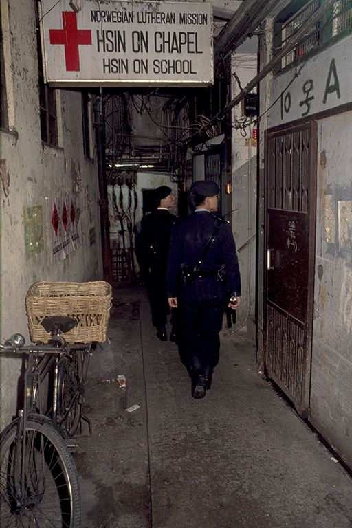 Policemen patrol one of the cleaner ground-floor alleys.