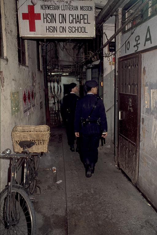 Policemen patrol one of the cleaner ground-floor alleys.